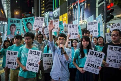 Nathan Law (C) speaks at a rally with Jousha Wong (centre L) and supporters in Causeway bay following Nathan Law's win in the Legislative Council election in Hong Kong on September 5, 2016. A new generation of young Hong Kong politicians advocating a break from Beijing looked set to become lawmakers for the first time on September 5 in the biggest poll since mass pro-democracy rallies in 2014. / AFP / ISAAC LAWRENCE        (Photo credit should read ISAAC LAWRENCE/AFP/Getty Images)